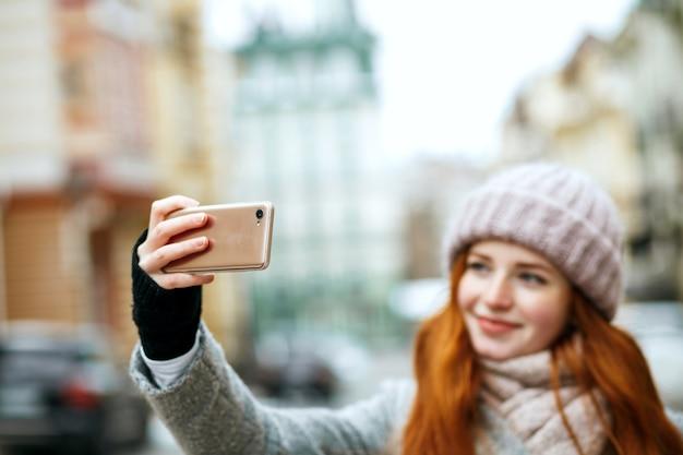 彼女の携帯電話で自分撮りをしている冬のアパレルの美しい生姜モデル。テキスト用のスペース