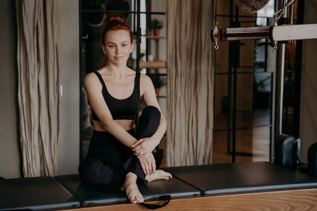 체육관이나 피트니스 스튜디오에서 운동 한 후 조용하고 편안한 위치에서 다리 주위에 팔이있는 캐딜락 기계에 앉아있는 스포츠웨어의 아름다운 생강 여자. 스포츠와 건강한 라이프 스타일