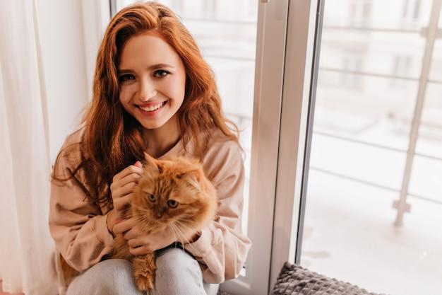 창 옆에 미소로 포즈를 취하는 아름 다운 생강 여자. 빨간 솜 털 고양이 들고 매력적인 여자의 실내 샷.