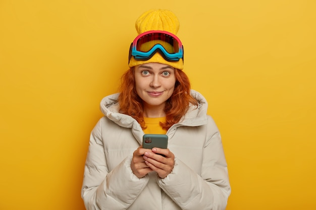 Beautiful ginger woman posts photos in social networks after awesome day, has active rest during winter, holds mobile phone, wears hat, coat and protective ski glasses, poses over yellow wall