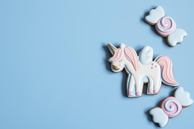 유니콘과 과자 모양의 어린이 파티를 위한 아름다운 진저브레드 쿠키는 평평하게 놓여 있습니다.