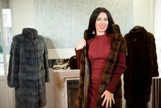 갈색 모피 코트에 포즈를 취하는 아름 다운 여자. 매장에서 럭셔리 모피 코트를 입은 여자.