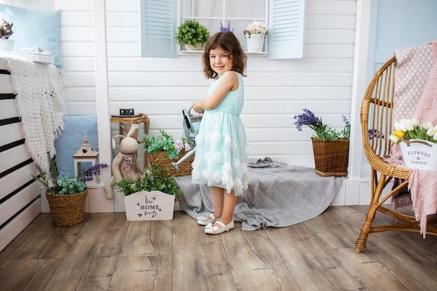 金属製のじょうろから白い家のベランダで花に水をまく裁判所で4-5歳の美しい少女