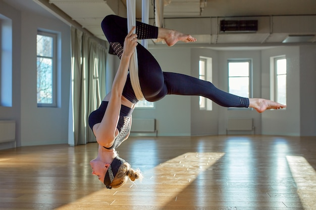 Beautiful girl aerial yoga trainer shows medutiruet on hanging lines upside down in a yoga room. concept yoga, flexible body, healthy lifestyle, fitness.