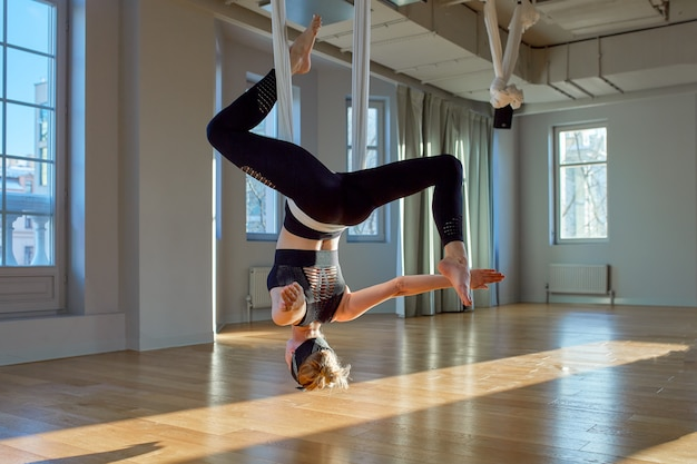 Beautiful girl aerial yoga trainer shows medutiruet on hanging lines upside down in a yoga room