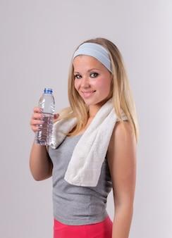 Красивая девушка после фитнеса с бутылкой с водой. с полотенцем и улыбкой.