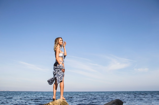 A beautiful girl alone stands on the seashore and enjoys the summer nature. minimalism.