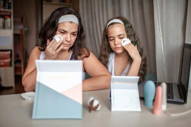 オンラインでタブレットで美容マスタークラスを見て、自分でスパの手順をしている美しい少女と彼女の母親、顔に滑らかなマスクを楽しんでいるママと娘、自宅の美容院