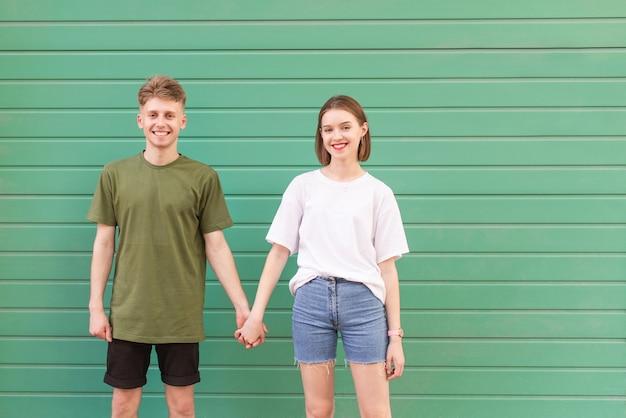 美しい少女と緑の上に立っている若い男