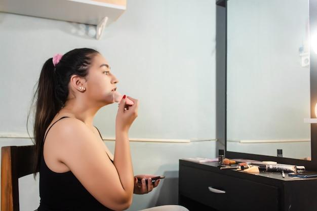 Красивая девушка, применяя пудру для макияжа перед зеркалом в своей комнате.