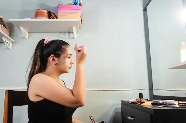 Красивая девушка, применяя пудру для макияжа в своей комнате.