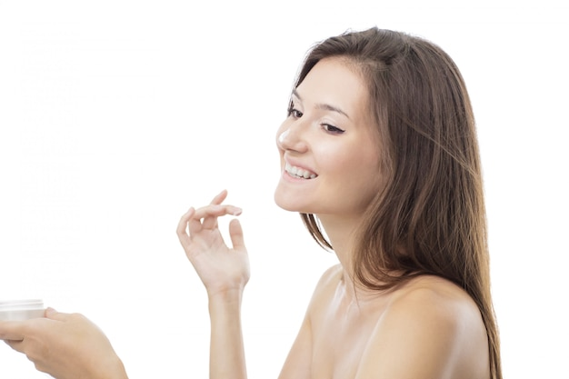 Beautiful girl applying mositurizing cream for face on her nose