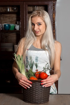 Beautiful girl in an apron holding a basket with vegetables in the kitchen