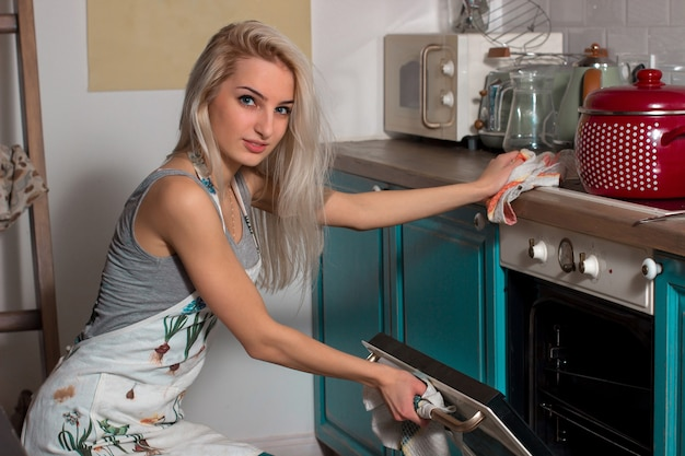 Beautiful girl in an apron in the kitchen opening the oven