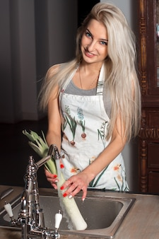 Beautiful girl in an apron in the kitchen washing the leeks