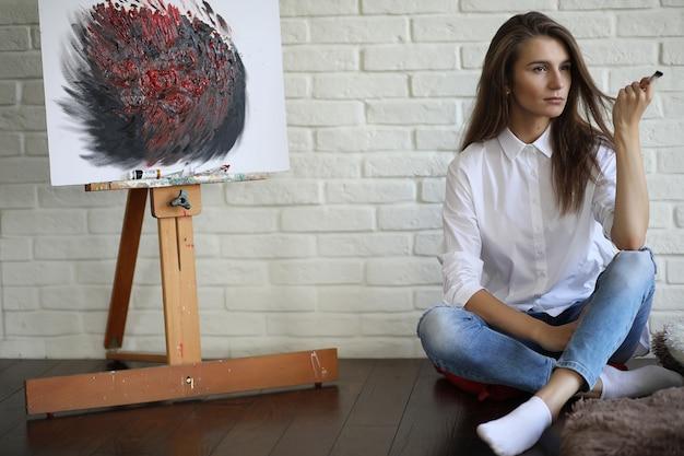 Художник красивая девушка за работой в творческой белой студии