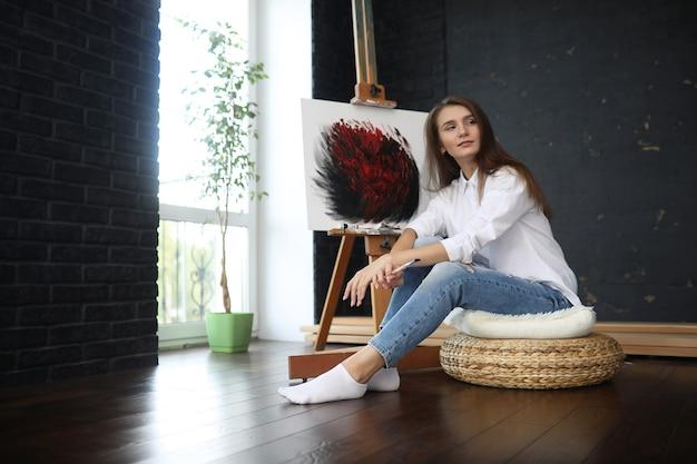 創造的な白いスタジオで働く美しい少女アーティスト