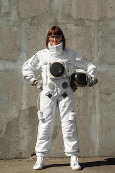 Beautiful girl astronaut without a helmet on the background of a gray wall. fantastic space suit.