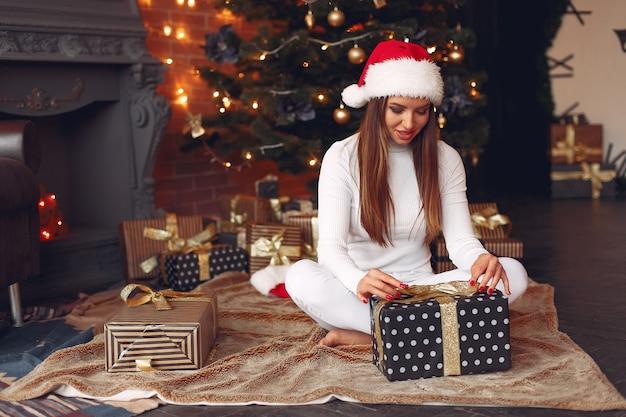 크리스마스 트리 근처 집에서 아름 다운 여자