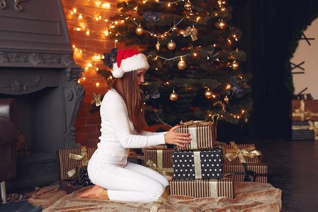 クリスマスツリーの近くに家で美しい少女