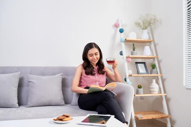 ソファに座って、本を読んで、コーヒーブレイクを持っている自宅で美しい少女