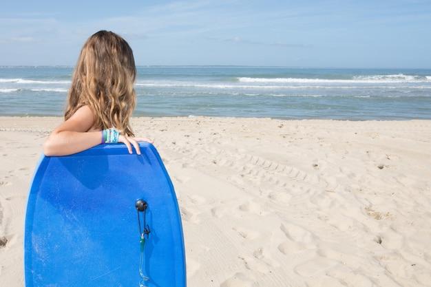 Красивая девушка на пляже с ее bodyboard с копией пространства