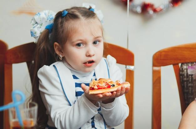 おいしいピザスライスを食べるお祭りの美少女