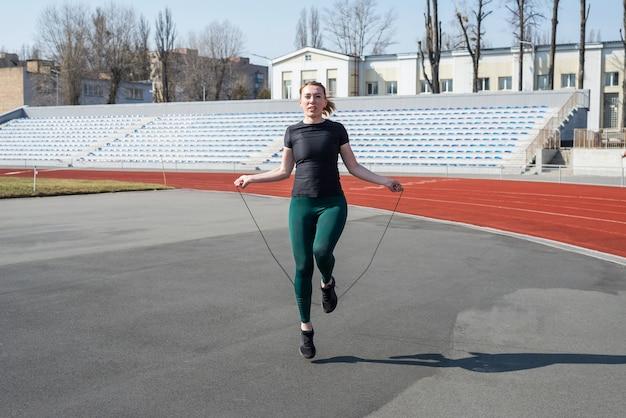 スタジアムで美しい少女。スポーツウェアのスポーツの女の子。縄跳びの女性