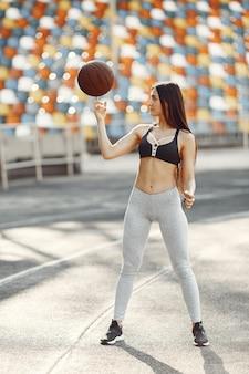 スタジアムで美しい少女。スポーツウェアのスポーツの女の子。バスケットボールのボールを持つ女性。
