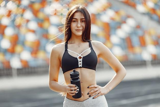 スタジアムで美しい少女。スポーツウェアのスポーツの女の子。水のボトルを持つ女性。