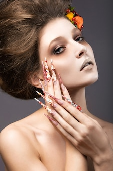 Beautiful girl in autumn image with long nails with bright and unusual make-up. picture taken in the studio on a gray background