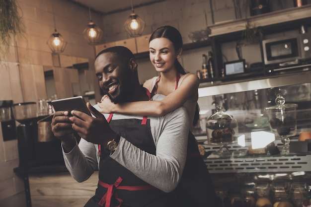 Beautiful girl barista hugs a man holding a tablet