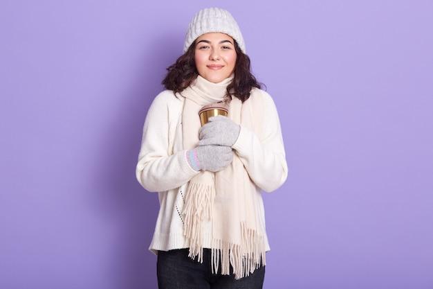 サーモマグで手を浴びて、寒い冬の天候で熱いお茶やコーヒーを飲むことを楽しんでいる美しい少女は、暖かいセーターを着ています。