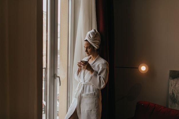 Beautiful girl in bathrobe and towel on her head looks thoughtfully out window with cup of tea in her hands.