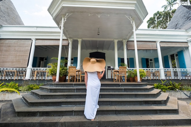 Beautiful girl in a big hat and white dress smiles outside an old colonial building on the island of mauritius.