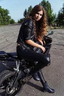 Красивая девушка-байкер возле спортивного мотоцикла