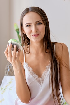 Beautiful girl biting cake while having breakfast in bed