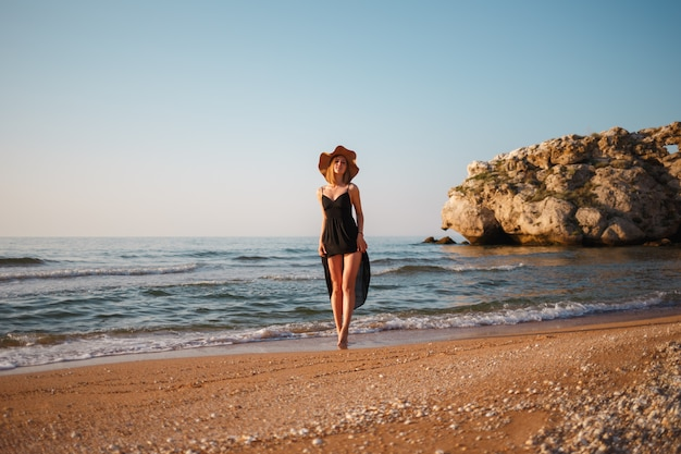 Beautiful girl in a black dress and hat walks along the sea sandy shore at sunset