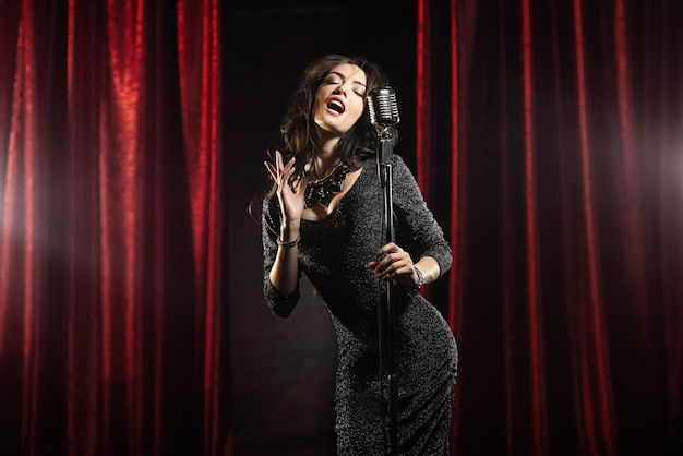 Beautiful girl in black dress singing in the microphone in the concert hall