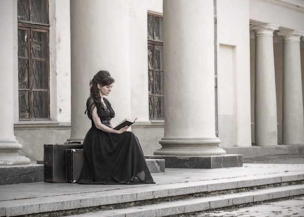 Beautiful girl in black evening dress sitting reading a book