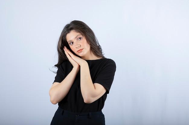 Bella ragazza in abito nero in posa per la fotocamera sul muro bianco.