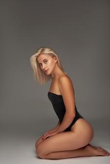 스튜디오에서 검은 bodysuit에서 아름 다운 소녀 금발