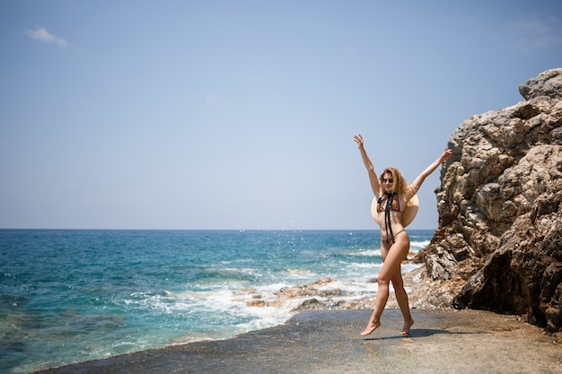 Beautiful girl blonde in swimsuit posing on the beach on the rocks