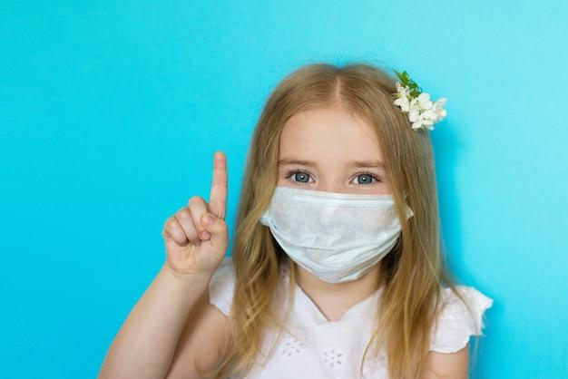 美しい少女、金髪、使い捨てマスク、青い背景を身に着けている