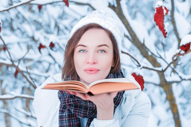 Красивая девушка дует на страницах книги