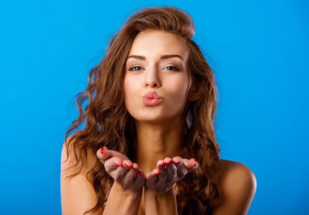 Beautiful girl blows a kiss to the front.
