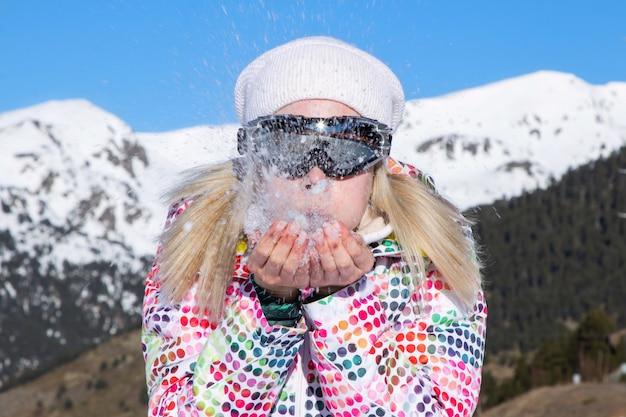 Красивая девушка сдувает с рук пушистый снег в солнечную погоду