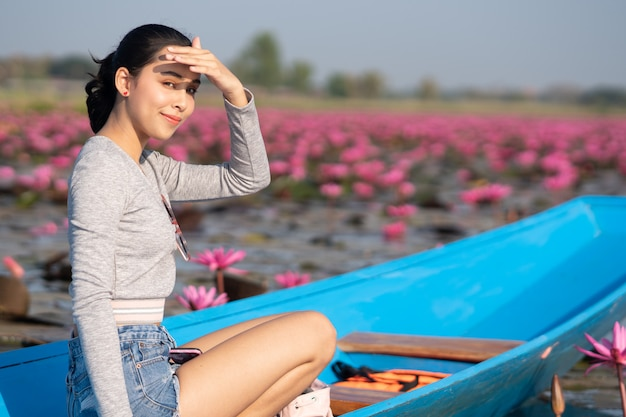 Beautiful girl on blue boat in pink lotus lake in the morning. sun protection.