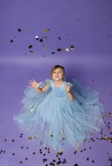 A beautiful girl in a blue dress catches confetti with her hands on purple