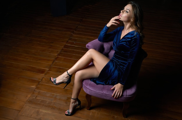 A beautiful girl in a blue dress is sitting on a purple chair in a dark room.